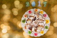 La torta y los macarons del Año Nuevo como reloj cerca de velas numeran 2017 Foto de archivo