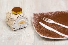 La torta y la placa en la tabla Fotografía de archivo