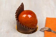 La torta y la toalla del esmalte del chocolate en la tabla Fotos de archivo libres de regalías