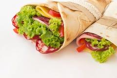 La tortilla rueda con la carne ahumada y las verduras en un blanco Imagen de archivo libre de regalías