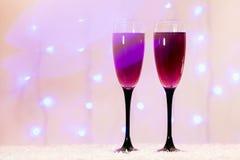 La tostada del fondo de los vidrios del champán empañó Año Nuevo rosado rojo de las luces Imagenes de archivo