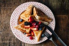 La tostada francesa sirvió con el jarabe y las bayas frescas Imágenes de archivo libres de regalías