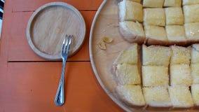 La tostada remató con mantequilla marrón en la tabla sobre los árboles anaranjados en placas de madera Y reparando el pequeño lin Imagen de archivo libre de regalías