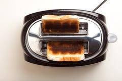 La tostadora negra, dos quemó rebanadas de pan negras Imagen de archivo libre de regalías