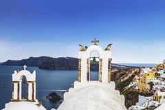 La tour de cloche de l'église orthodoxe grecque sur les eaux de fond de la mer Égée dans la ville d'Oia sur l'île de Santorini Images stock