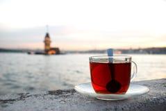 La tour de la jeune fille par tasse de thé Photos stock