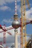 La tour de TV à Berlin derrière des grues de construction Image stock
