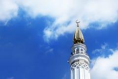 La tour droite (minaret) de la mosquée dans un jour ensoleillé contre le ciel bleu Photos stock
