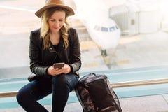 La touriste de femme dans le chapeau, avec le sac à dos s'assied à l'aéroport près de la fenêtre, utilise le smartphone À l'arriè Image stock