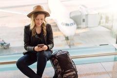 La touriste de femme dans le chapeau, avec le sac à dos s'assied à l'aéroport près de la fenêtre, utilise le smartphone À l'arriè Images libres de droits