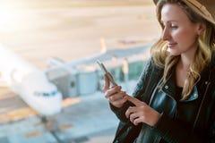 La touriste de femme dans le chapeau s'assied à l'aéroport près de la fenêtre, utilise le smartphone Dans l'avion de blanc de fon Photos libres de droits