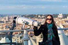 La touriste de femme presque se tient aux jumelles sur la ville Rome photo stock