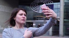 La touriste de Madame font le selfie sur le smartphone près du Parlement européen à Bruxelles belgium Mouvement lent banque de vidéos