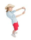 La touriste drôle de fille dans le chapeau de paille fait la photo Photographie stock libre de droits