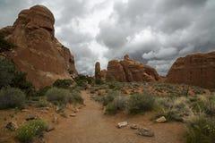 La traînée et le ciel nuageux aux diables font du jardinage, des voûtes parc national, Moab Utah photo libre de droits