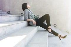 La trabajadora del negocio se sienta en la escalera en postura atractiva de la relajación, fotos de archivo