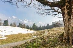 La traccia di escursione raggiunge la capanna della montagna Grande vista alle montagne innevate Immagini Stock Libere da Diritti