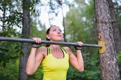 La traction convenable de formation de femme se lève sur la barre horizontale en parc de ville dehors Photo stock