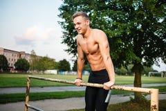 La traction musculaire de jeune homme lève la barre horizontale Séance d'entraînement de rue Image libre de droits