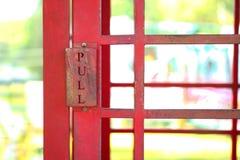 La TRACTION se connectent la porte en acier rouge de la cabine de téléphone rouge de vintage photographie stock libre de droits