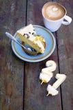 La tranche de bougie de witn de gâteau d'anniversaire numéro un et deux avec la tasse de latte sur la table en bois dans la lumiè image stock