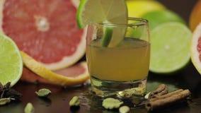 La tranche de chaux tombe dans une tasse en verre avec un cocktail alcoolique banque de vidéos