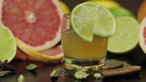 La tranche de chaux tombe près d'un verre avec un cocktail alcoolique banque de vidéos