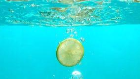 La tranche de citron tombe dans l'eau bleue avec des bulles en dessus de table sous-marin de tir de mouvement lent banque de vidéos