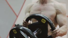 La transición tiró del hombre muscular resuelto que ponía las láminas pesadas en barbell y que levantaba en gimnasio almacen de video