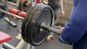 La transition a tiré de l'homme musculaire déterminé mettant les tôles fortes sur le barbell et se soulevant dans le gymnase Jeun clips vidéos