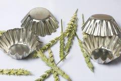 La transitoire des céréales a dispersé sur un fond blanc Parmi les formes en métal pour les gâteaux de cuisson Sur un fond blanc photographie stock