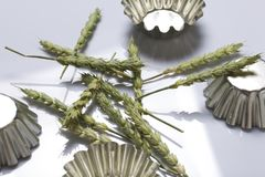 La transitoire des céréales a dispersé sur un fond blanc Parmi les formes en métal pour les gâteaux de cuisson Sur un fond blanc photos libres de droits