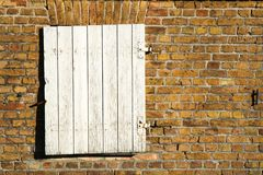 La trappe en bois blanche fermée de fenêtre avec le métal rouillé s'articule sur un mur de briques rougeâtre jaune sale d'une vie photo libre de droits