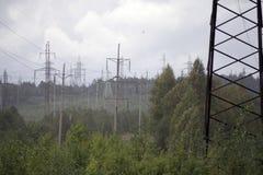 La trasmissione elettrica ad alta tensione si eleva piloni dell'elettricità e linee elettriche sul campo verde Immagine Stock