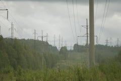 La trasmissione elettrica ad alta tensione si eleva piloni dell'elettricità e linee elettriche sul campo verde Fotografia Stock Libera da Diritti