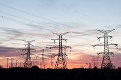 La trasmissione elettrica torreggia su (piloni) al crepuscolo Immagini Stock Libere da Diritti