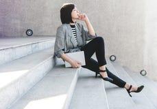 La travailleuse active d'affaires s'asseyent sur l'escalier dans la posture de relaxation avec t Photos stock