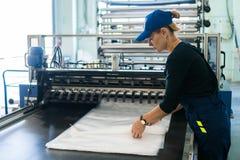 La travailleuse dans la production du conditionnement en plastique plie des produits finis image stock