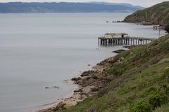 La trayectoria de la playa ambla a lo largo de los acantilados abajo a los embarcaderos largos del océano para los barcos de pesc Foto de archivo libre de regalías