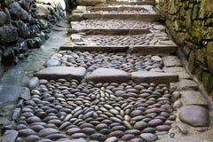 La trayectoria de piedra redonda, intensifica, la pared de piedra ambos lados Imágenes de archivo libres de regalías