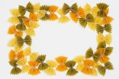 La tri pasta del farfallino di colore rasenta il fondo bianco Fotografie Stock