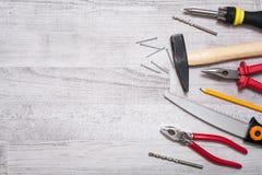 La trousse d'outils du marteau, clous, tournevis, pinces, Pen And a vu sur un de table en bois regardent vers le bas avec l'espac Photo stock