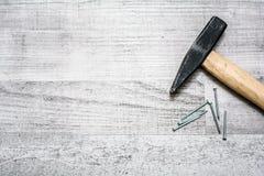 La trousse d'outils du marteau et les clous sur un de table en bois regardent vers le bas avec l'espace de copie Images libres de droits