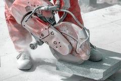 La tuile de marbre de coupe de travailleur avec la main électrique a vu Photographie stock libre de droits