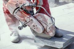 La tuile de marbre de coupe de travailleur avec la main électrique a vu 2 Photos libres de droits