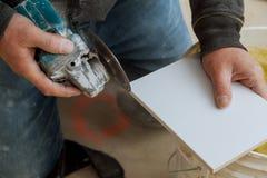La tuile professionnelle de coupe de travailleur d'homme avec la circulaire a vu ?lectrique photographie stock