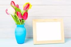 La tulipe colorée de printemps rouge fleurit dans le vase bleu intéressant et le cadre vide de photo sur le fond en bois clair co Images stock
