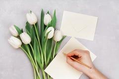 La tulipe de ressort fleurit et la main d'homme signant une carte sur la vue supérieure en pierre grise de table dans l'apparteme Photos stock