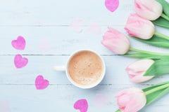 La tulipe de ressort fleurit et tasse de café sur la vue supérieure bleue en pastel de table Beau petit déjeuner de ressort le jo Photos stock