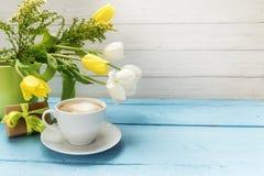 La tulipe de tasse de café, jaune et blanche fleurit dans un vase et un a verts Image stock